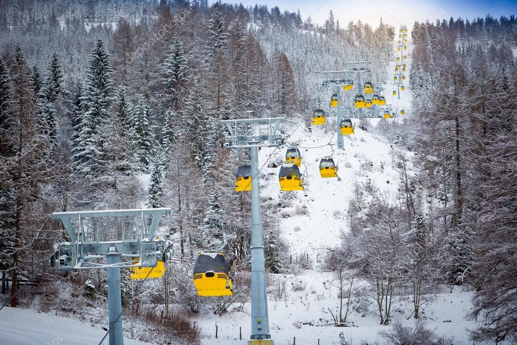 panoramic shot of long line of cable cars on ski slope