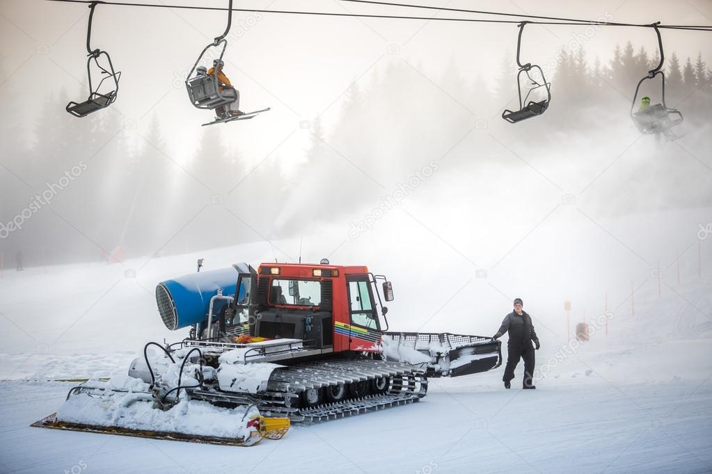 snow cleaning machine working on ski slope under cable chairs