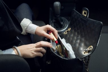 Closeup shot of female driver searching for lipstick in purse