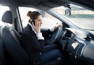 concentrated woman talking by phone and driving car