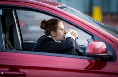 tired woman driving car and looking through window