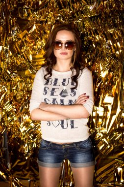 confident sexy woman in sunglasses posing on golden background