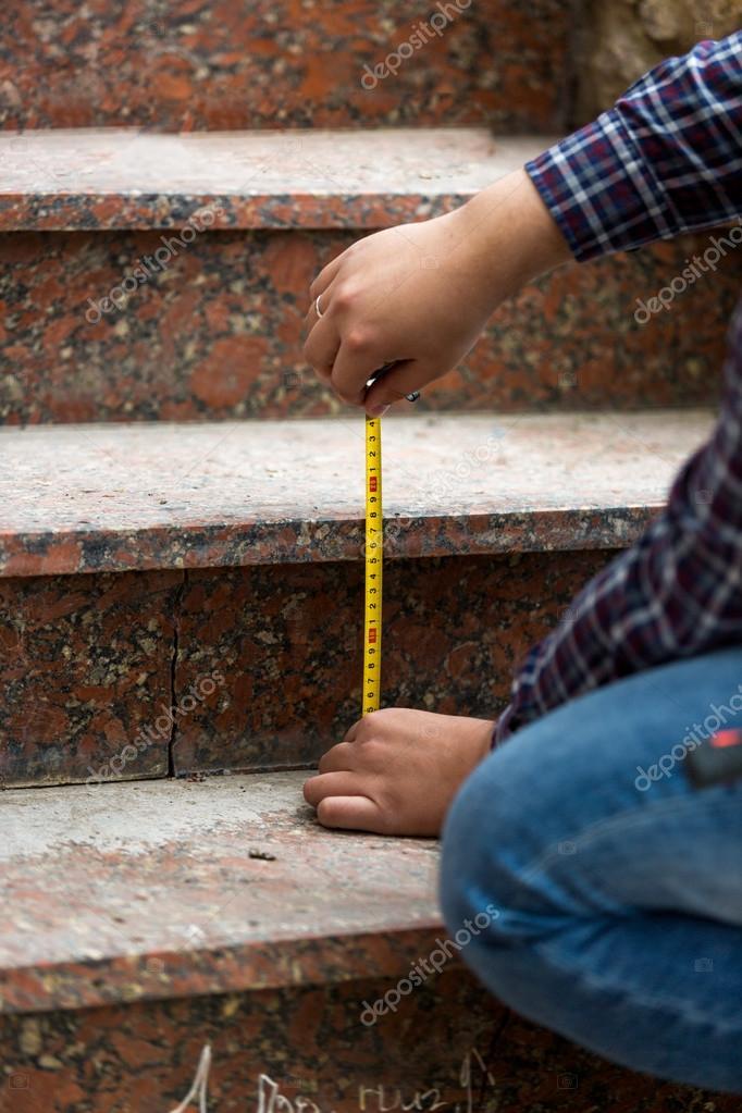 closeup del trabajador midiendo altura de escalones de piedra u foto de stock