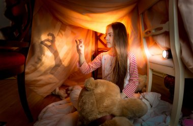 little girl playing in shadow theater in bedroom at night