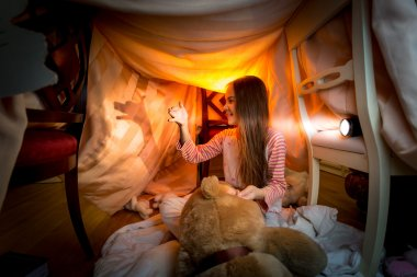 little girl making theater of shadows in bedroom at night