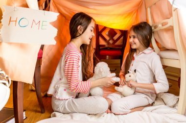 smiling girls playing in house made of blankets at bedroom