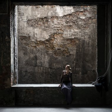 Grungy photo of lonely woman sitting at window in old building