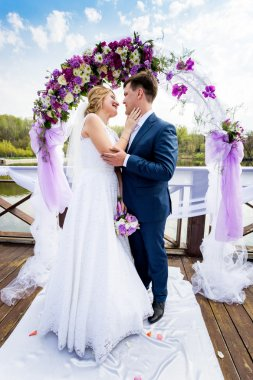 bride and groom hugging under decorated flower arch