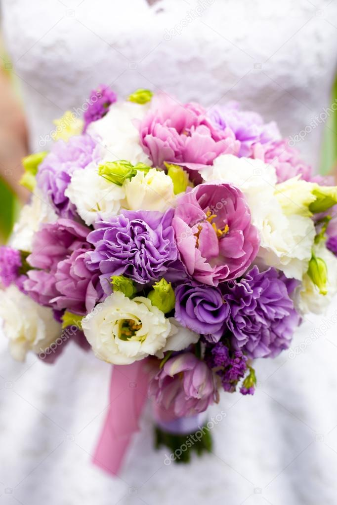 bride holding bridal bouquet with white, pink and purple flowers ...