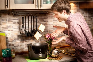 young man trying to catch toasts popping out of toaster
