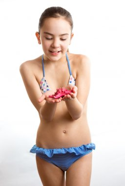 Little girl in swimsuit playing with red starfish
