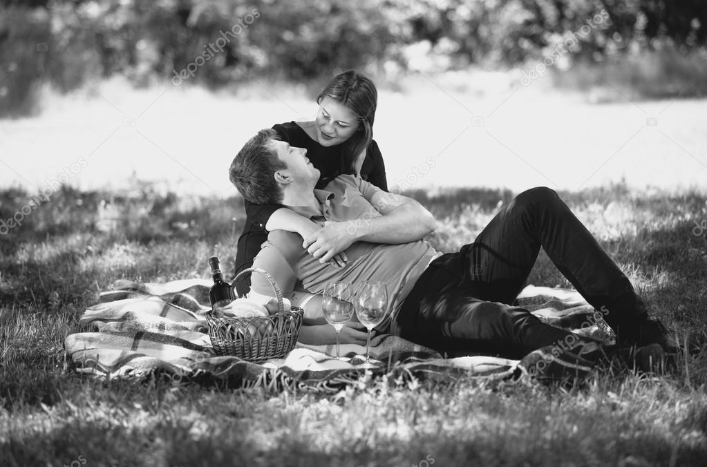 Black and white portrait of romantic couple embracing on picnic