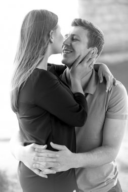 Black and white portrait of happy couple in love kissing at rive