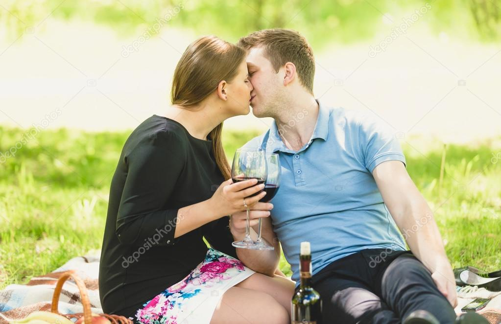 Romantic couple kissing and drinking wine at picnic
