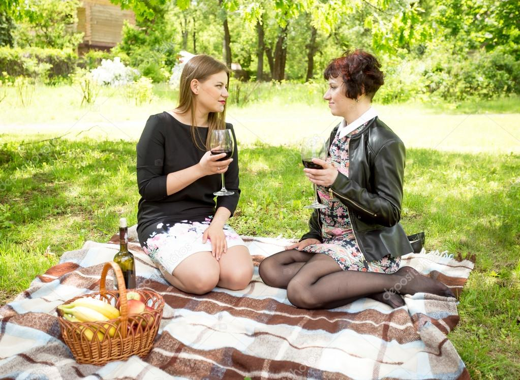 Two women drinking wine and talking at picnic