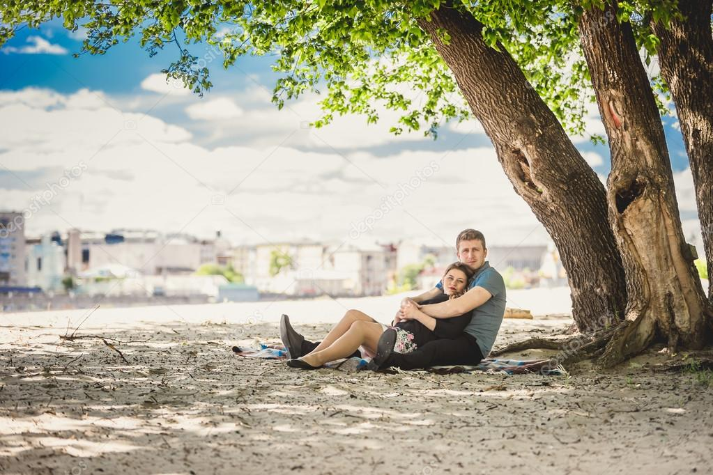 Toned photo of beautiful couple in love relaxing under tree