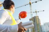 Closeup of engineer posing on building site with orange hardhat