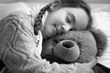 Black and white portrait of cute dreaming girl hugging teddy bea