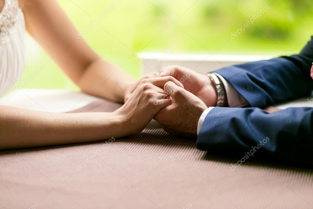 Closeup of bride and groom holding hands on table at restaurant