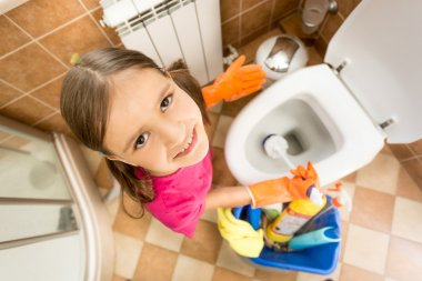 portrait of cute little girl cleaning toilet with brush