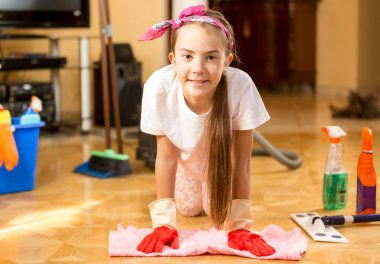 Portrait of smiling girl cleaning wooden floor with rag