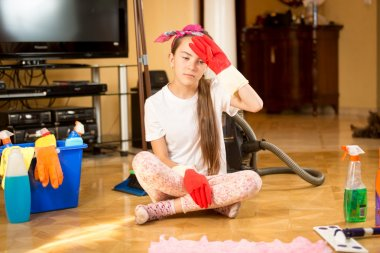 tired teenager girl cleaning wooden floor at living room