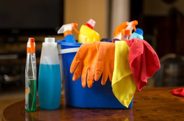 Closeup of cleaning chemicals, gloves and rags lying in plastic