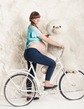 Toned photo of pregnant woman riding on bike with big teddy bear