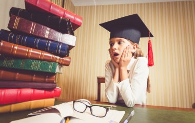 amazed smart girl in graduation cap looking at big heap of books