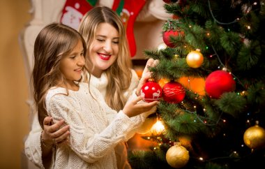 smiling mother decorating Christmas tree with daughter
