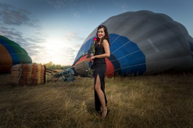 young woman posing at meadow next to hot air balloons
