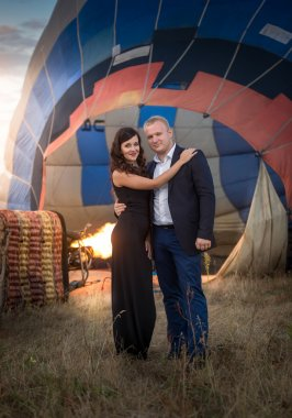 romantic couple hugging against hot air balloon at meadow