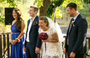 laughing bride and groom posing at outdoor wedding ceremony