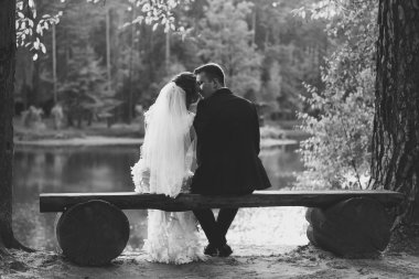 Monochrome photo of bride and groom kissing on bench at riverban