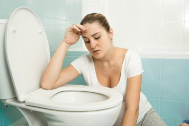 young woman feeling sick and leaning on toilet