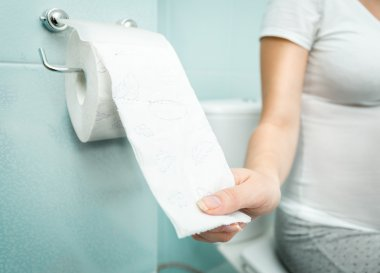 Closeup of woman sitting on toilet and using toilet paper