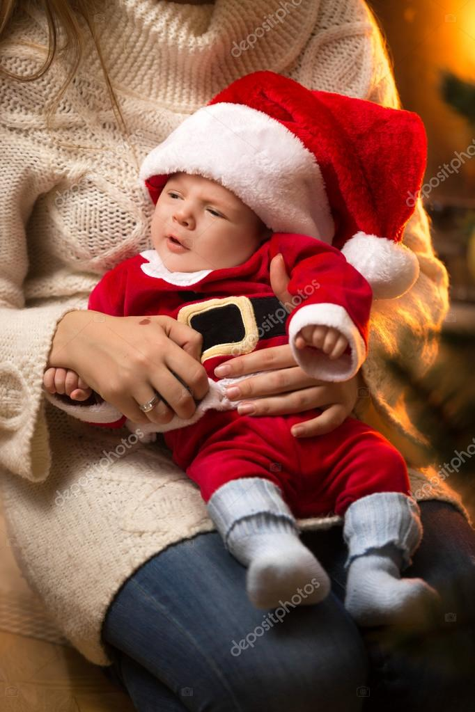 Mother holding newborn baby boy in santa costume at fireplace stock photo
