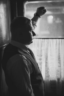 portrait of handsome man in suit looking out of window in retro