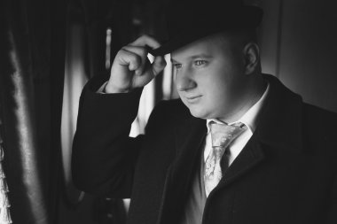 black and white portrait of man in bowler hat looking out train