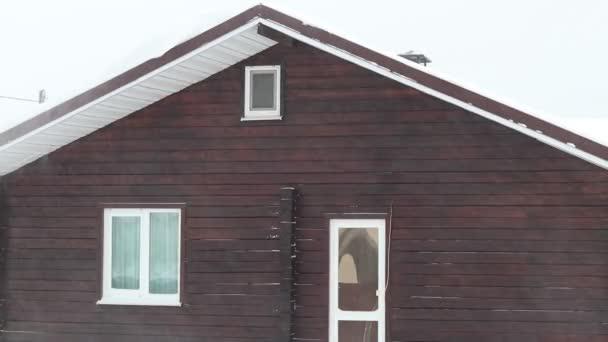 Straßenbeleuchtung. Es schneit sehr stark. Ein Teil des Hauses ist sichtbar. Der Wind bläst Schneeflocken vom Dach