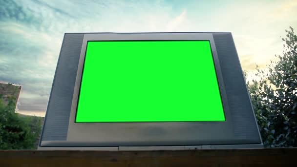 Régi Televízió zöld képernyővel a szabadban. Kicserélheti a zöld képernyőt a felvételre vagy képre, amit akar. Meg tudod csinálni a Keying hatás After Effects vagy bármely más videó szerkesztő szoftver (nézd meg útmutatók a YouTube-on).