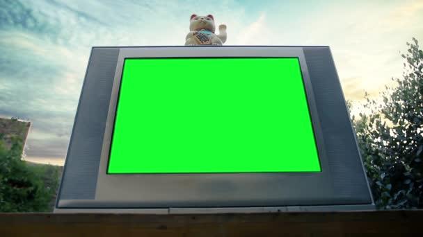 Maneki Neko Macska és Régi TV Zöld vászonnal. Alacsony látószögű. Kicserélheti a zöld képernyőt a felvételre vagy képre, amit akar. Meg tudod csinálni a Keying hatás After Effects vagy bármely más videó szerkesztő szoftver.
