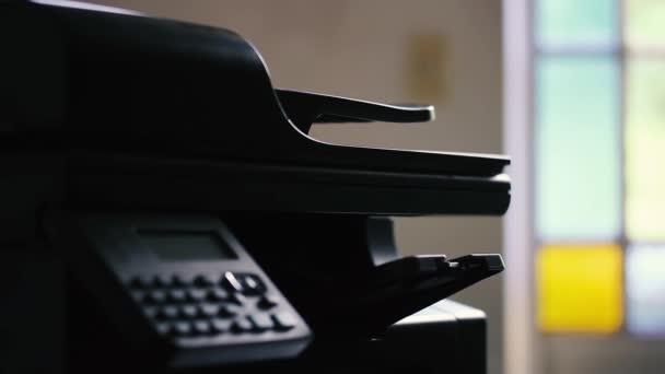 Bürodrucker drucken ein weißes Blatt Papier. Nahaufnahme.