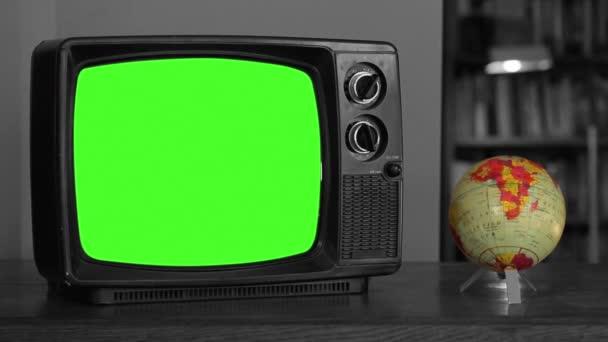 Vintage Television with Green Chroma Screen near a Rotating Terrestrial Globe Map. Fekete-fehér Tone. Közelről. Kicserélheti a zöld képernyőt a felvételre vagy képre, amit akar. Meg tudod csinálni a Keying hatás After Effects.