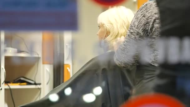Hairdresser in face mask cuts woman hair in evening. blonde in barber chair