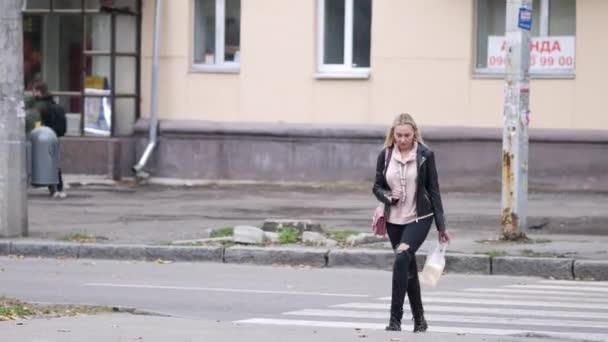 Young woman crosses road. Blonde in black jeans walks along pedestrian crossing.