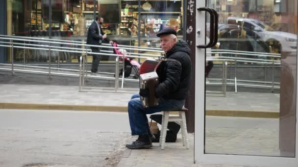 Straßenmusiker spielt Knopfakkordeon. Älterer Basker virtuoser Akkordeonspieler