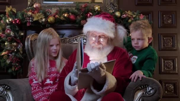 Šťastné děti poslouchají vánoční příběh od Santa Clause. Santa čte knížku malým dětem, z knihy září jasné magické světlo. Veselé Vánoce a šťastný Nový rok. Zázraky času.