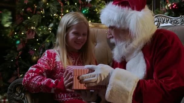 Santa Claus dává dárek magie box dívka, jasné světlo svítí z krabice na malou blondýnu sedí v křesle v pokoji s krbem a vánoční stromeček zdobené v pokoji.