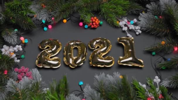 Karácsonyi mágia sötét háttér arany számok 2021 megállapított közepén díszített fenyő ágak és színes fényes lámpák koszorúk körül kerülete. Újévi kártya háttér.